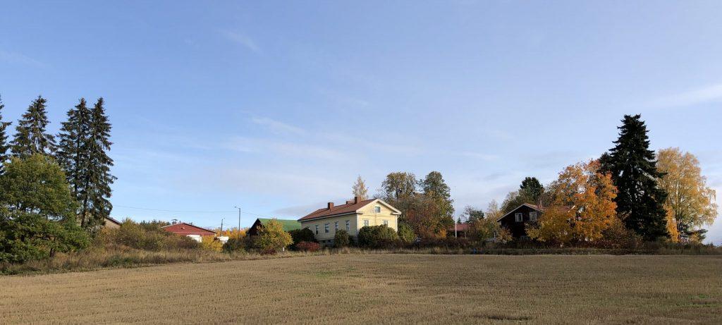 maatila rakennuksineen syksymaisemassa