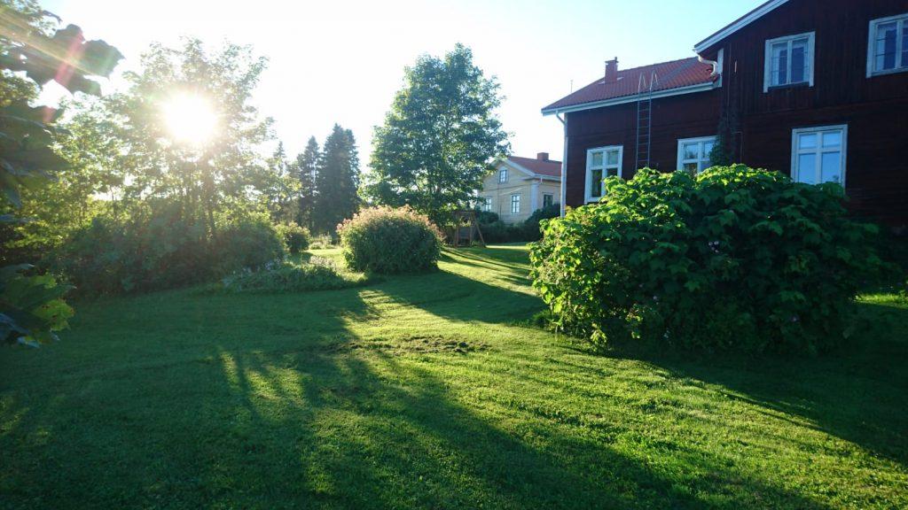 puutarha ja maatilan asuinrakennuksia auringonpaisteessa