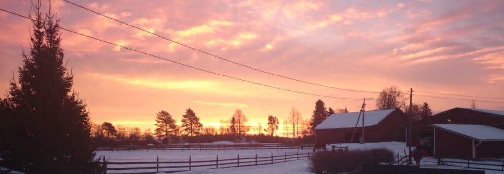 talvimaisema maatilalta punainen aamutaivas taustalla