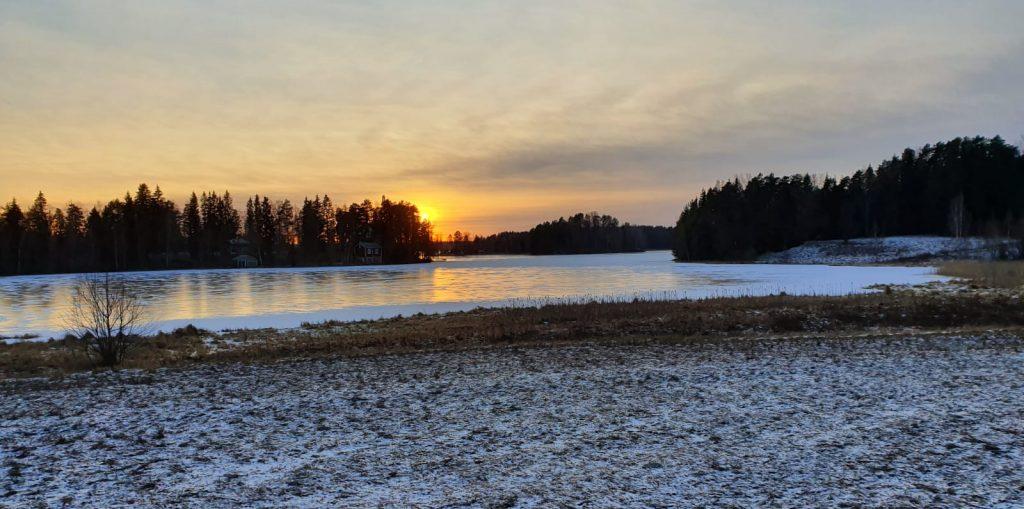 talvimaisema pakkasessa jaatynyt jarvi ja iltapaivan aurinko